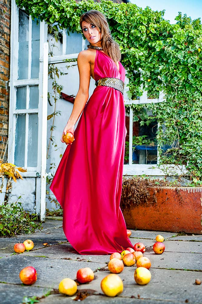 model portfolio photo in red dress surrounded by fallen apples