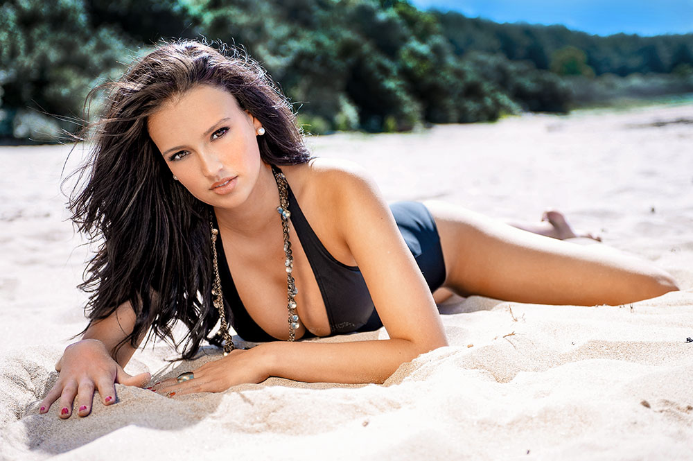 female model in black swimsuit on a beach