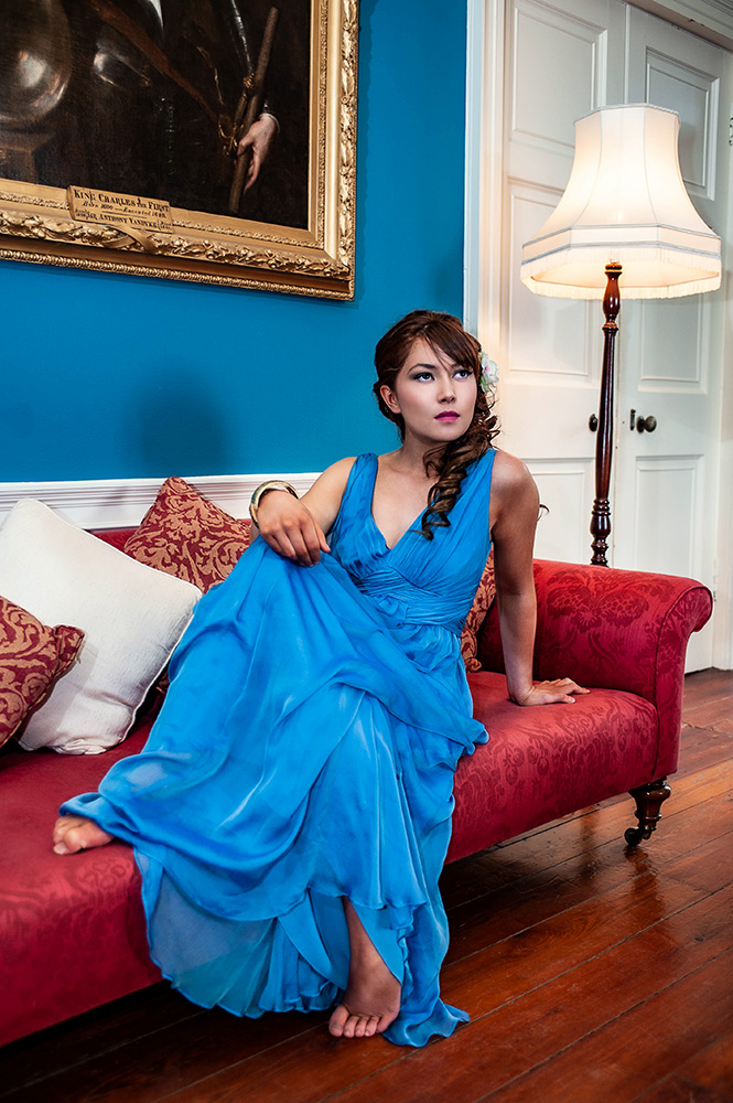teenager in blue dress on red couch